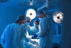 Team of professional doctors performing operation in surgery room