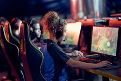 Team of professional gamers participating in global eSport tournament, side view. Mixed race teenage girl wearing headphones looking at PC screen and playing online video game
