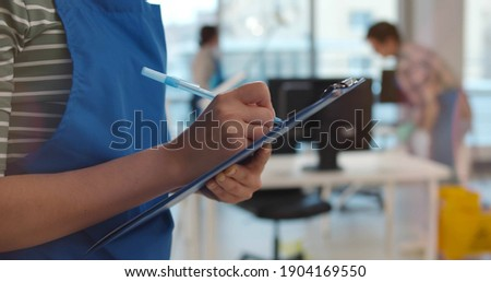 Team of professional janitors in uniform cleaning office. Close up of woman cleaner checking list on clipboard supervising cleaning service team work in modern office Stock photo ©