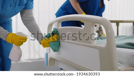 Team of professional janitors using equipment disinfecting hospital ward. Nurses in uniform cleaning furniture in empty clinic room. Healthcare and hygiene concept
