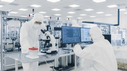 Team of Research Scientists in Sterile Suits Working with Computers, Looking Under Microscope and Industrial Machinery in the Laboratory. Product Manufacturing Process: Pharmaceutics, Semiconductors,