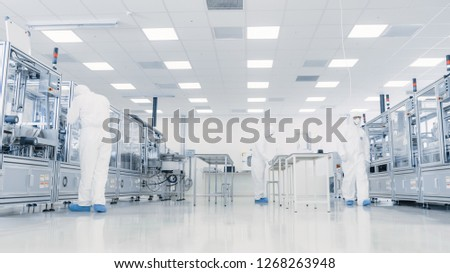 Team of Research Scientists in Sterile Suits Working with Computers, Microscopes and Industrial Machinery in the Laboratory. Product Manufacturing Process: Pharmaceutics, Semiconductors, Biotechnology