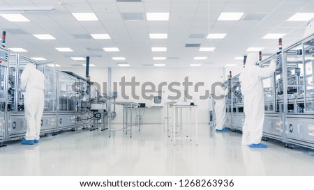 Team of Research Scientists in Sterile Suits Working with Computers, Microscopes and Modern Industrial Machinery in the Laboratory. Product Manufacturing Process: Pharmaceutics, Semiconductors