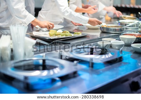 Team of restaurant chef helping each other to finish the good food for customer in five star hotel Stock photo ©