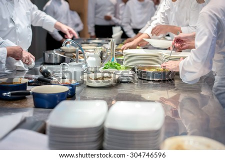 Team of restaurant chef helping each other to finish the good food for customer in five star hotel