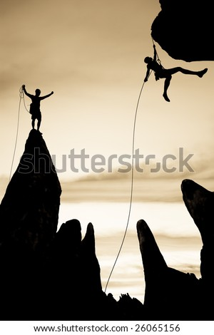 Team of rock climbers silhouetted on the summit,  dangle in midair rappelling from a rock spire in The Sierra Nevada Mountains.