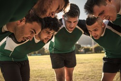 Team of rugby players in huddle discussing their tactics. Professional rugby team in huddle during the game.