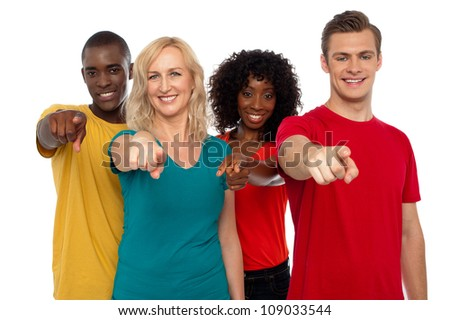 Team of smiling teenagers indicating at you isolated over white background