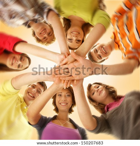 Team Of Smiling Teens Staying Together And Looking At Camera