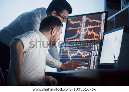 Team of stockbrokers are having a conversation in a dark office with display screens. Analyzing data, graphs and reports for investment purposes. Creative teamwork traders.