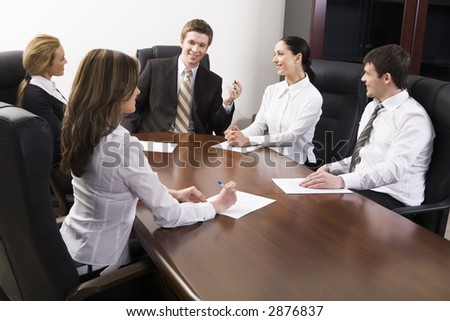 Team of successful business people are sitting at the table and discussing