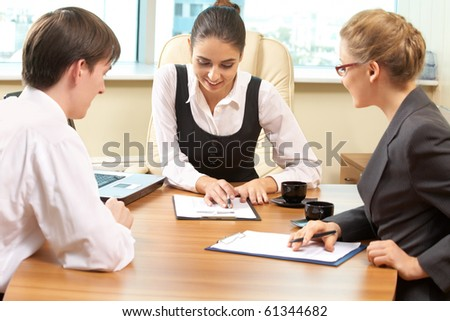 Team of successful business people sitting at the table and talking to each other #61344682