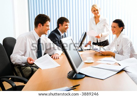 Team of successful business people sitting at the table with monitors, notepad, papers and white cup on it talking to each other discussing important questions