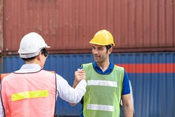 Team of supervisor and man worker in uniform and wearing yellow safety helmet and handshake while standing on commercial dock site with container box from cargo freight ship for import export