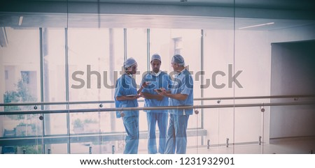 Team of surgeons discussing over digital tablet in hospital corridor