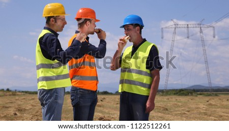 Team of Technician Engineers Men Eating Sandwich Lunch Time with Electric Pillar Powerline Infrastructure #1122512261