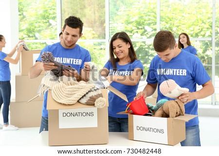 Team of teen volunteers collecting donations in cardboard boxes indoors
