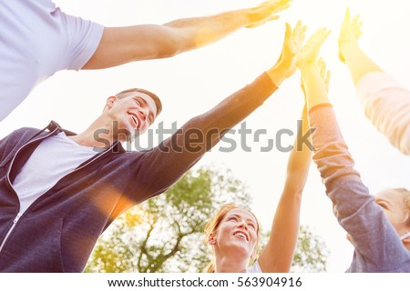Team of teenagers High Five in the air in summer as friendship and success concept