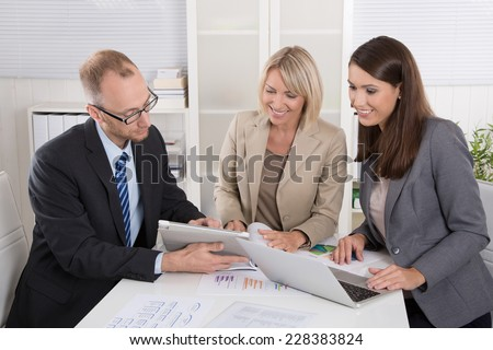 Team of three business people sitting together at desk in a meeting. - Shutterstock ID 228383824