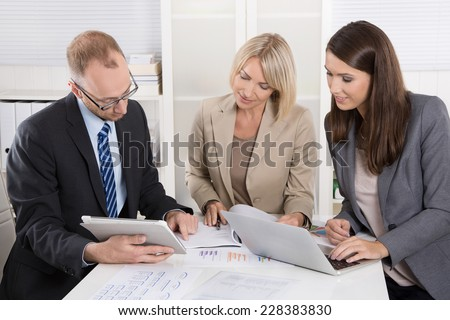 Team of three business people sitting together at desk in a meeting. - Shutterstock ID 228383830