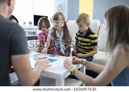 Team of three children and team of three adults play board games at home. Deck of cards and playing cards laid out in row on table. Photo stock ©