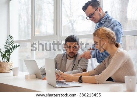 team of three coworkers in stylish studio