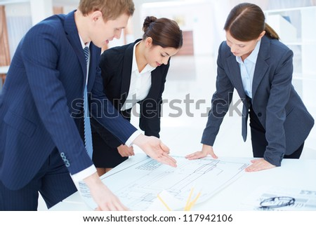 Team of three engineers discussing blueprint at meeting