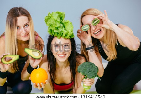 Team of three sports smiling fitness women with avocado, orange, salad, kiwi are covering their eyes enjoying useful products. Healthy, mindfulness food, eating nutritional concept. Foto d'archivio ©