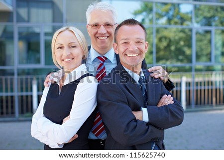 Team of three successful business people smiling together