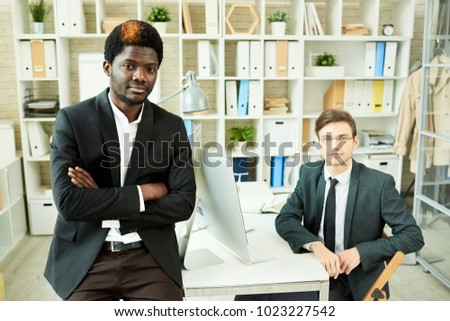 Team of two business professionals posing in modern office leaning om desk confidently with arms crossed and smiling at camera, copy space