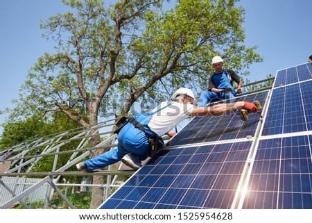 Team of two professional technicians connecting solar photo voltaic panel to metal platform on clear blue sky background. Stand-alone solar system installation, efficiency and professionalism concept.