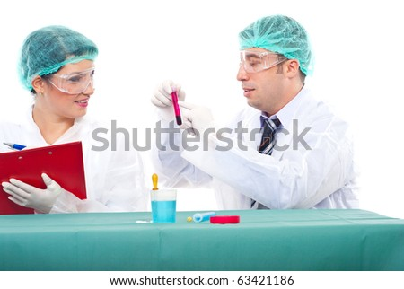 Team of two scientists people examine blood tube .Man pointing on tube and woman writing in clipboard - stock photo