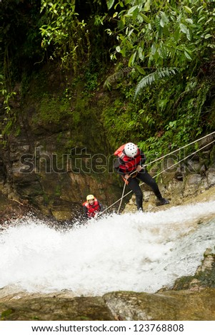 team of two young womens wearing waterproof equipment descending a waterfall