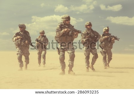 Team of United states airborne infantry men with weapons moving patrolling desert storm. Sand, blue sky on background of squad, sunlight, front view