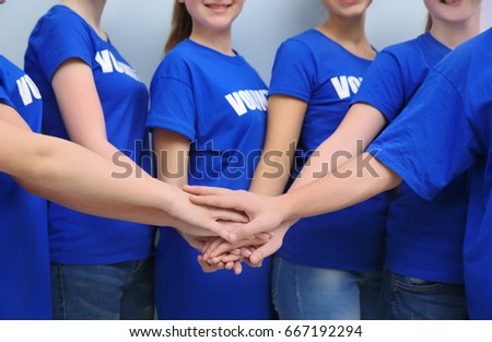 Team of volunteers putting their hands together as symbol of unity, on color background #667192294