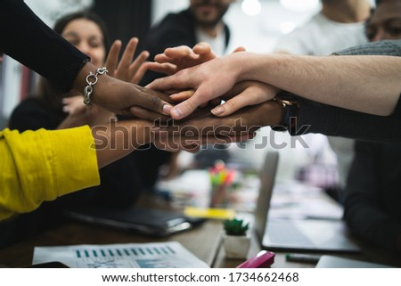 Team of work of creative designers showing unity with their hand together during meeting. Business and team work concept.