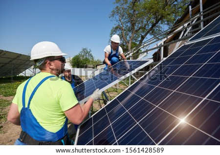 Team of workers lifting heavy solar photo voltaic panels to high steel platform on bright sunny day. Stand-alone solar panel system installation, efficiency and professionalism concept.