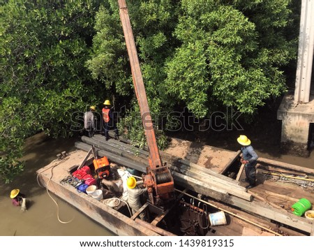 Team of workers pull the concrete pillars out of the water on the iron pontoon with crane. River coast reconstruction, Thailand