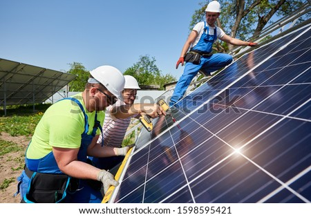 Team of workers taking measurement and connecting solar photo voltaic panels to high steel platform under blue sky. Stand-alone solar panel system installation, efficiency and professionalism concept.