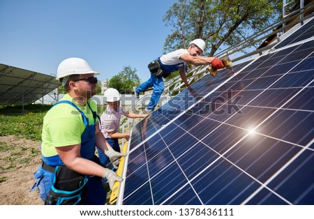 Team of workers taking measurement and installing solar photo voltaic panels to high steel platform under blue sky. Stand-alone solar panel system installation, efficiency and professionalism concept.