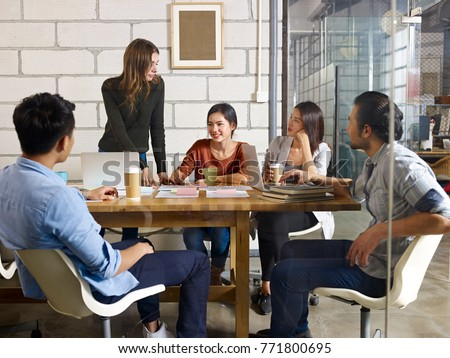 team of young asian and caucasian entrepreneurs meeting in office discussing business plan in office. - Shutterstock ID 771800695