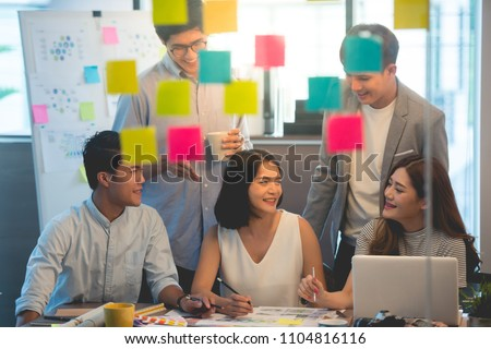 Team of young Business employees collaborating on creating presentation using colorful stickers with notes.behind glass wall,flare light