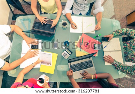 Team of young business people at a meeting - Start up conference, group of investors planning a new strategy - Office desk with computers,phones,notes and other supplies