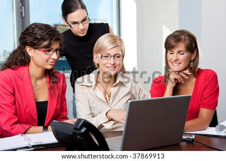 Team of young businesswomen sitting at table in meeting room, using laptop computer, smiling.