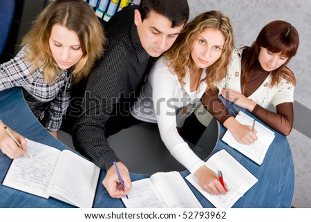 Team of young colleagues taking notes on corporate meeting