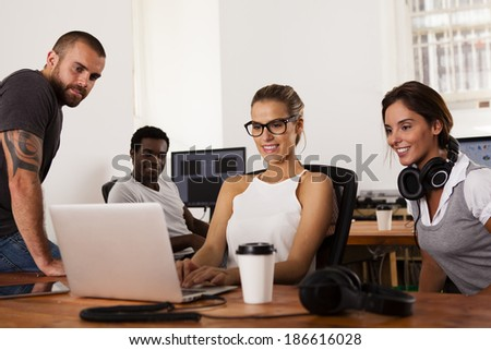 Team of young entrepreneurs looking at a laptop computer in a tech startup office