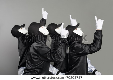 Team of young guys in masks pointing their fingers up.