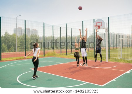Team of young intercultural friends or students working out on basketball court stock photo