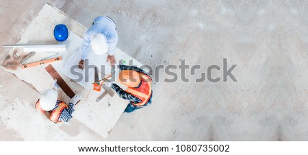 Team of young man and woman engineer and architects working, meeting, discussing,designing, planing, measuring layout of building blueprints in construction site floor at factory.top view & copy space