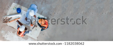 Photo of  Team of young man and woman engineer and architects working, meeting, discussing,designing, planing, measuring layout of building blueprints in construction site floor at factory.top view & copy space